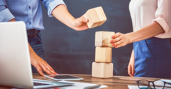 Business people stacking wooden blocks