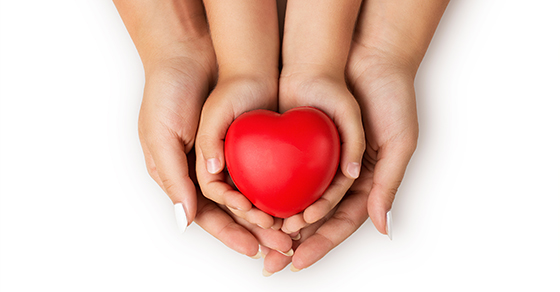 Adult hands and child hands holding a heart