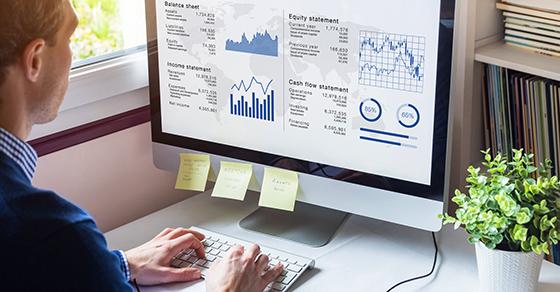 Man at computer looking at charts and graphs