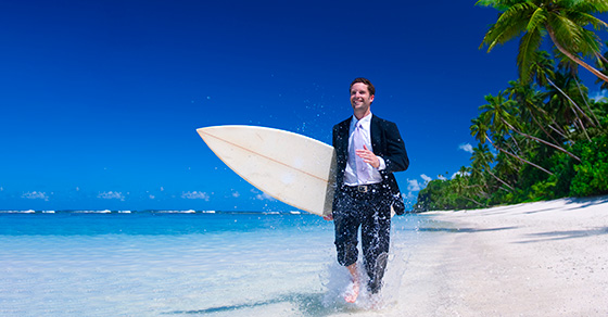Business man on beach holding a surf board
