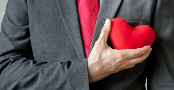 Man holding a plush heart next to chest