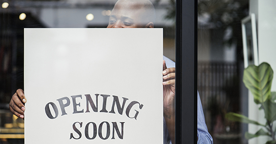 Female turning sign on business door that reads OPENING SOON